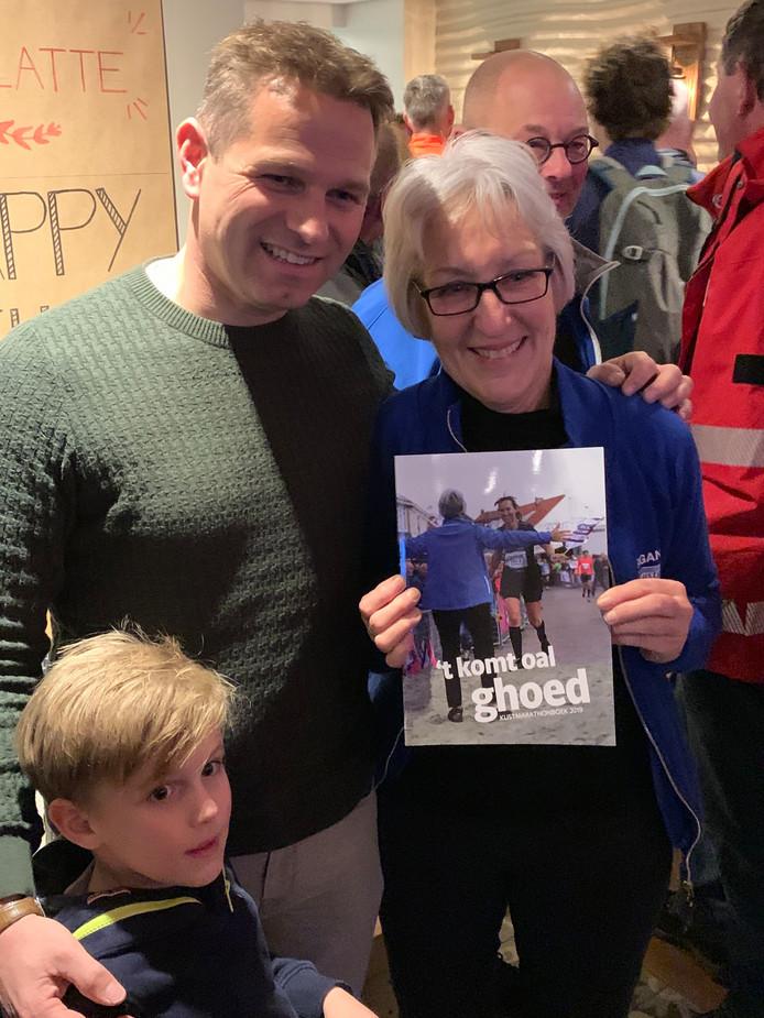 Gedeputeerde Jo-Annes de Bat reikt Lenie Lievense het kustmarathonboek uit.