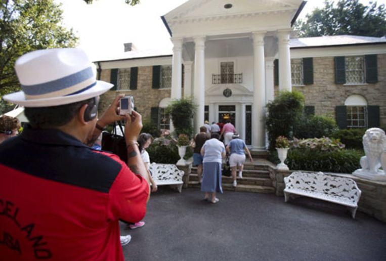 Een fan neemt tijdens een herdenkingstour in het Amerikaanse Memphis een foto van het bedevaartsoord en voormalig woonhuis van Elvis. Het is vandaag dertig jaar geleden dat Elvis op 42-jarige leeftijd overleed. (EPA) Beeld