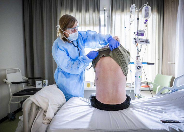 Een arts luistert naar de longen van een patiënt die herstelt na een ic-opname in het HMC Westeinde ziekenhuis.  Beeld ANP
