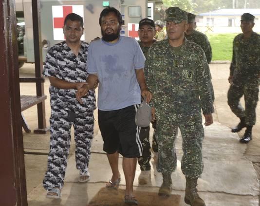 Een van de ontsnapte gijzelaars, Rod Pagaling, wordt door militairen begeleid naar hun legerkamp