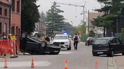 Auto ramt geparkeerde wagen en gaat over de kop