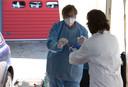 De afnemer, in geval Irma Thus, pakt twee wattenstaafjes uit een geprepareerd bakje. Deze wordt aangereikt door een assistent.