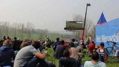 Volkse sfeer op de Paterberg: wachtend op de renners kijken naar grote videoschermen, met bier en croque monsieurs