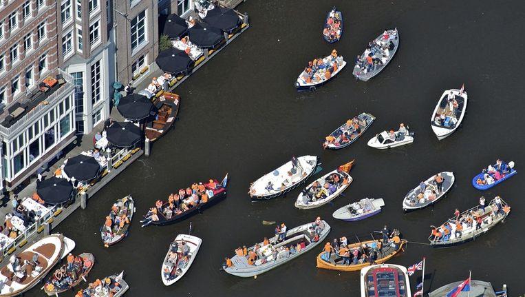 Een luchtfoto van bootjes met feestvierders op de gracht in Amsterdam tijdens Koninginnedag. Beeld anp
