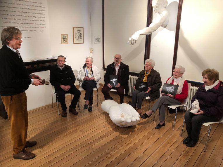 Gie Mateusen geeft de senioren uitleg over de kunstwerken.