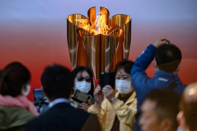 Mensen maken selfies voor de olympische vlam in Japan.