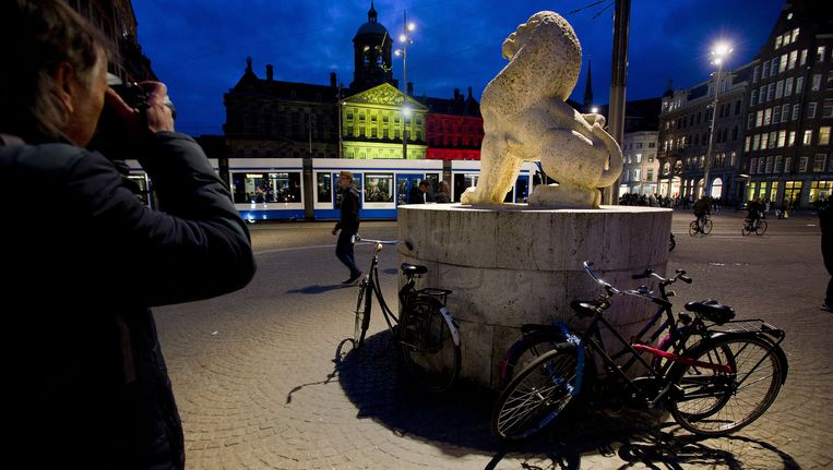 De avond na de aanslagen werd het Paleis op de Dam in de Belgische kleuren verlicht. Beeld ANP