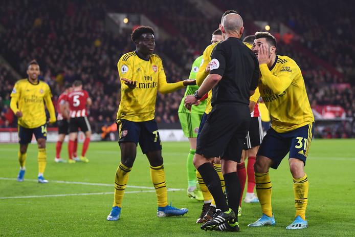 Arsenal-spelers protesteren bij arbiter Mike Dean na de gele kaart voor Bukaya Saka (midden).