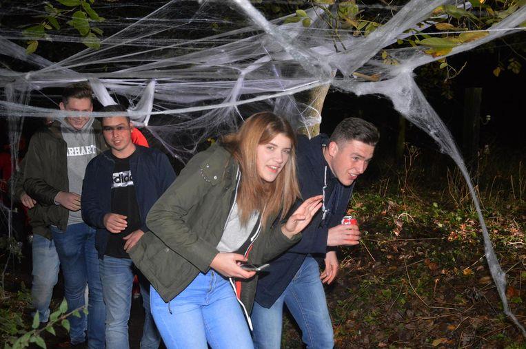 De bezoekers moeten hier onder spinnenwebben door, terwijl lichten flikkeren en er griezels op de weg staan.