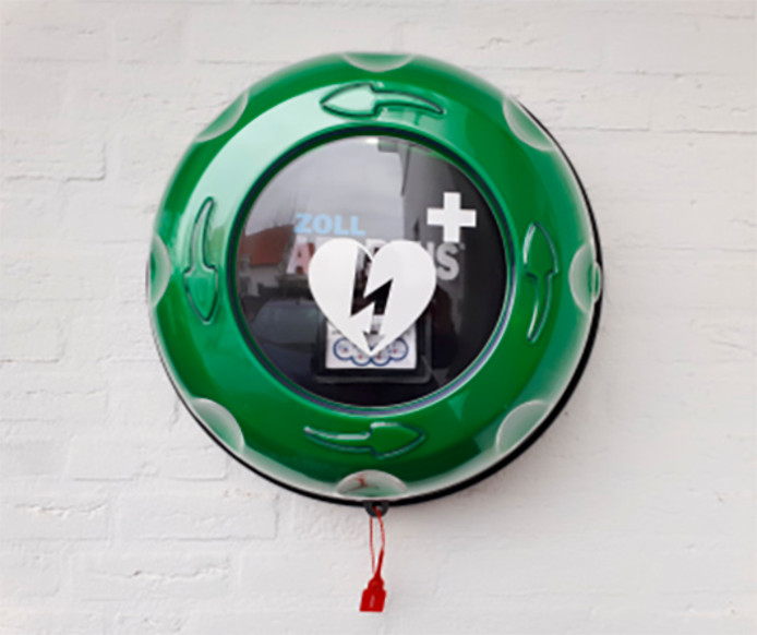 Een AED hangt in een kastje aan de muur.
