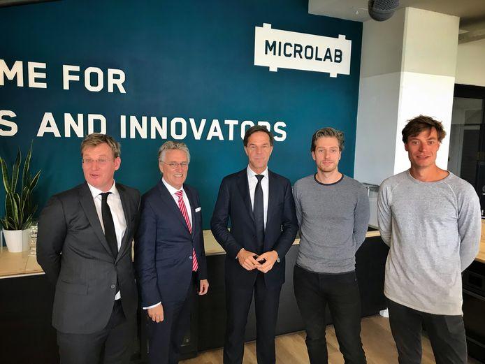 Vlnr. Brainport-directeur Paul van Nunen, burgmeester John Jorritsma, premier Mark Rutte en Rik en Luuk Visser van Microlab.