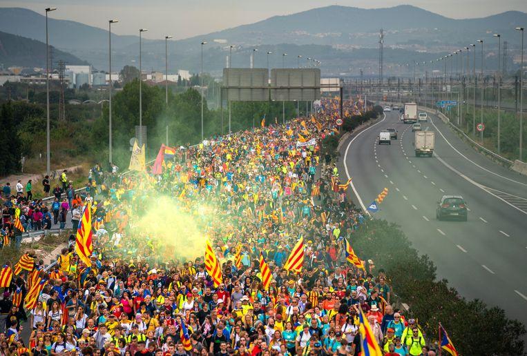 Catalanen lopen over de snelweg naar de Spaanse stad Barcelona. Beeld Freek van den Bergh / de Volkskrant
