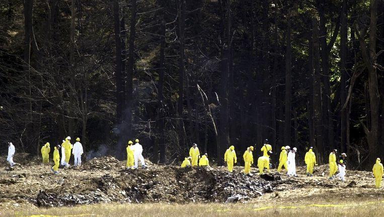 Onderzoekers zoeken naar overblijfselen van passagiers van 'flight 93', in de bossen van Pennsylvania op 12 september 2001. © Reuters Beeld