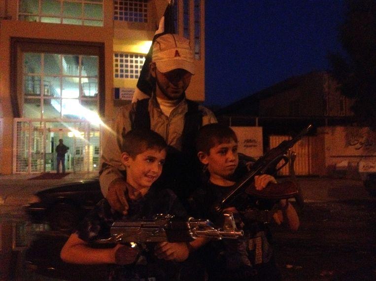 Een Al-Kaidalid heeft twee kinderen automatische wapens gegeven, terwijl zij kijken naar een parade van Isis-strijders in de Iraakse stad Mosoel op 23 juni. Beeld AP