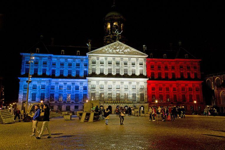 Zondagavond werd op initiatief van de gemeente het Paleis op de Dam aangelicht met het blauw, wit en rood van de Franse driekleur. Beeld ANP