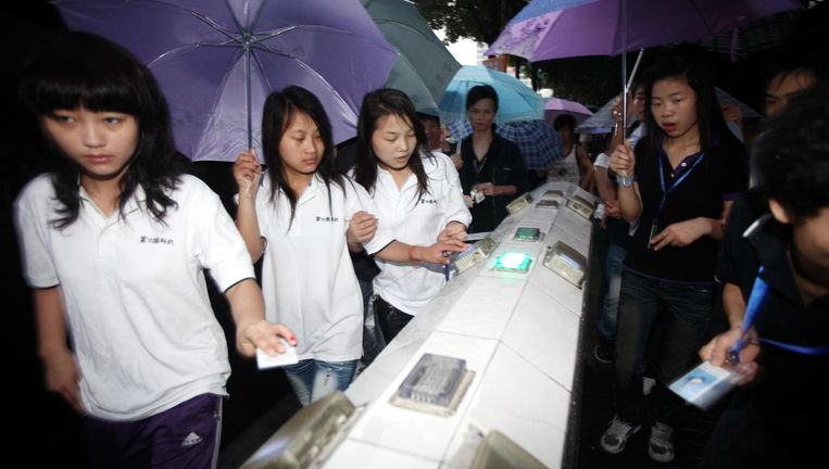 Werknemers van Foxconn in de fabriek in Shenzhen. Beeld Wang yishu