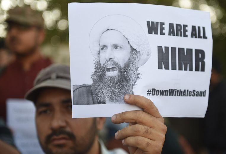 Demonstranten in Pakistan houden een foto omhoog van de geëxecuteerde Nimr al-Nimr. Beeld afp