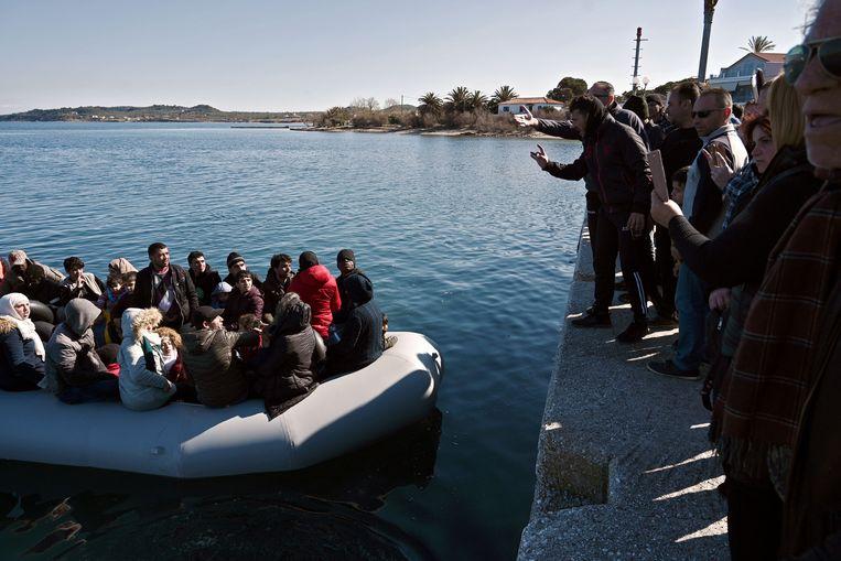 Bewoners van het eiland Lesbos proberen te voorkomen dat een boot met vluchtelingen aanmeert.  Beeld AFP