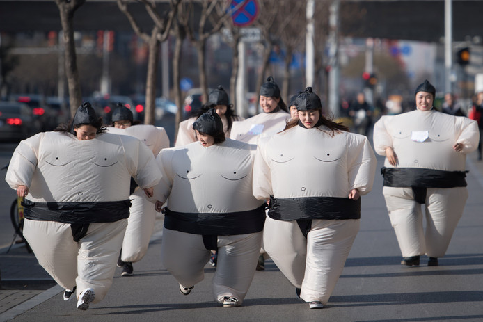 Vrouwen verkleed als sumoworstelaars doen mee aan een Sumo-run in het Chinese Taiyuan. Foto Stringer/Reuters