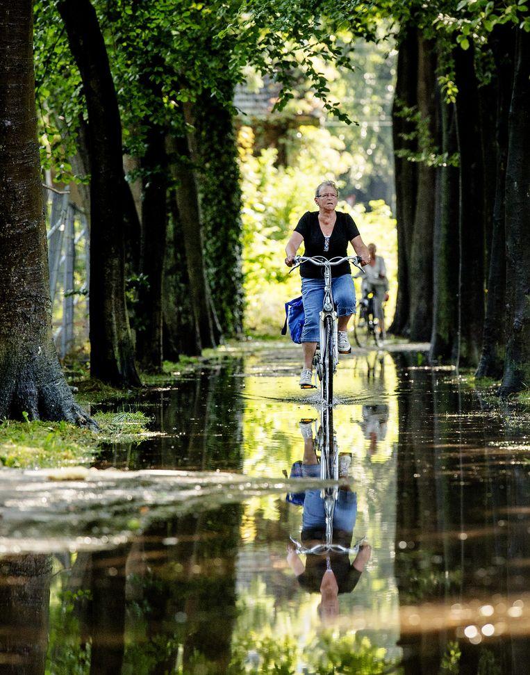 Een fietser rijdt door een diepe plas in het bos in Baarn. Beeld anp