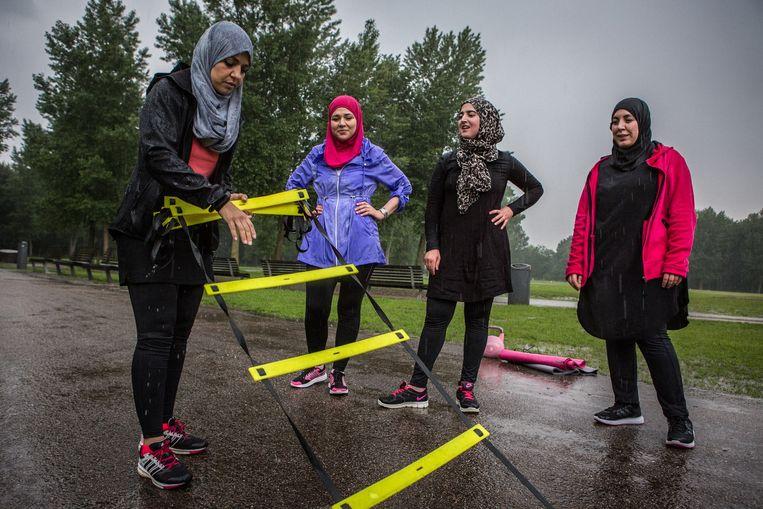 Sportende moslima's in het Kralingse Bos, Rotterdam. Links coach Mounia Abbadi. Beeld Cigdem Yuksel