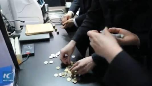 Het bankpersoneel is uren in de weer om de 3000 munten schoon te maken, te sorteren en te tellen.