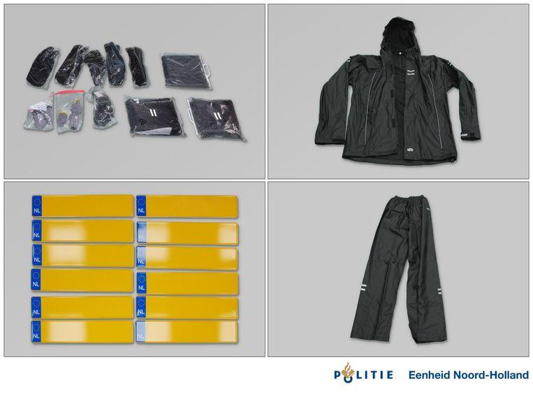De aangetroffen regenpakken, bivakmutsen en enkele van de kentekenplaten. Beeld Politie
