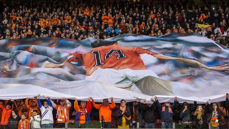 Supporters houden een groot spandoek omhoog met de afbeelding van Johan Cruijff tijdens een minuut stilte in de veertiende minuut stilte van hun oefenduel in de Amsterdam ArenA Beeld anp