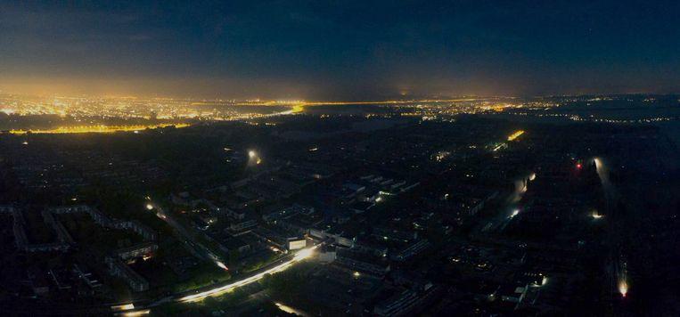 Vanuit een vliegtuig is zaterdagnacht te zien hoe Amsterdam Zuidoost donker is. Even later zal ook Schiphol (aan de horizon) door de stroomstoring worden getroffen. Beeld