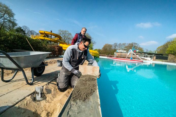 Laatste klusjes aan Goffertbad voor de opening op 28 april: het betegelen van de badrand.