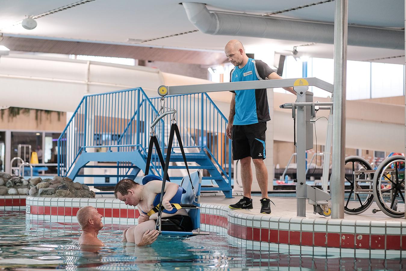 Bert van Horen (links) begeleidt zijn zoon Wouter in de nieuwe rolstoellift van het Lentebad in Zevenaar.