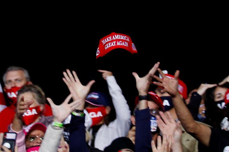 Op 19 september, tijdens een Republikeins campagne-evenement in North Carolina, werd dit rode MAGA-petje richting het publiek gegooid. Beeld Tom Brenner /Reuters