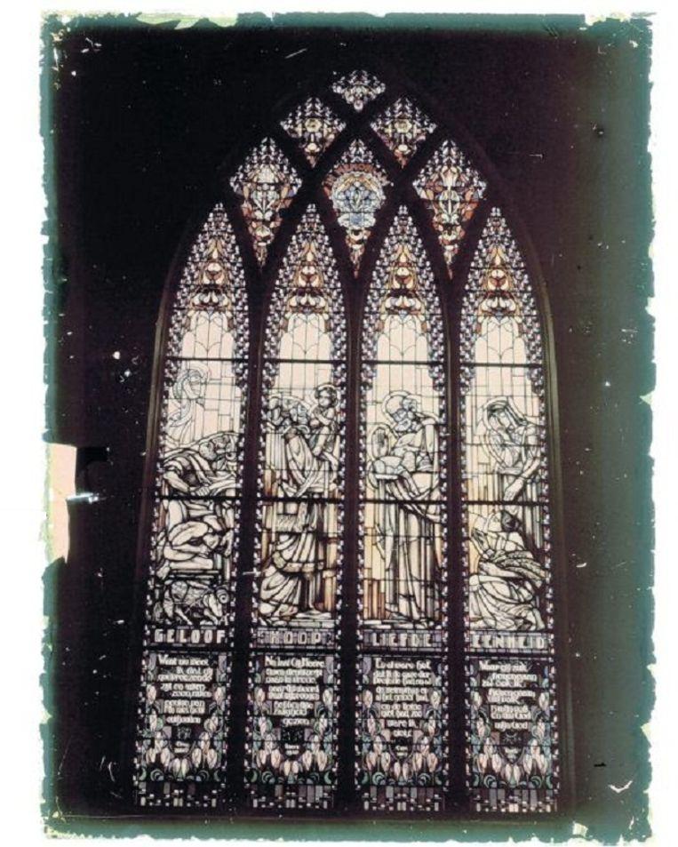 Historische kleurenopname, van fotograaf Leendert Blok, van een art deco kerkraam met geloof, hoop, liefde, en eenheid. Beeld HH