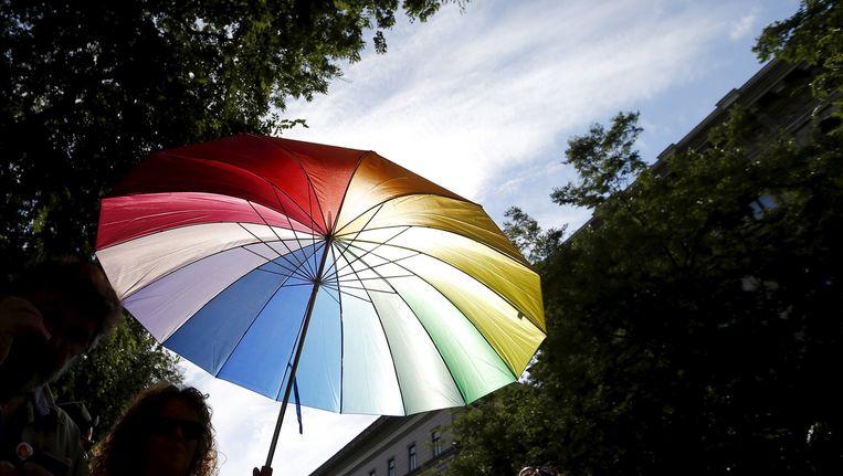 Een vrouw houdt een regenboogparaplu vast tijdens de Gay Pride in Budapes, begin juli. Beeld reuters