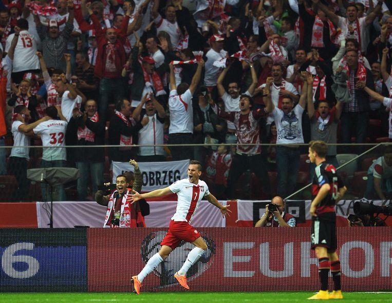 Arkadiusz Milik (M) juicht na zijn doelpunt namens Polen tegen Duitsland. Uitslag 2-0 Beeld anp