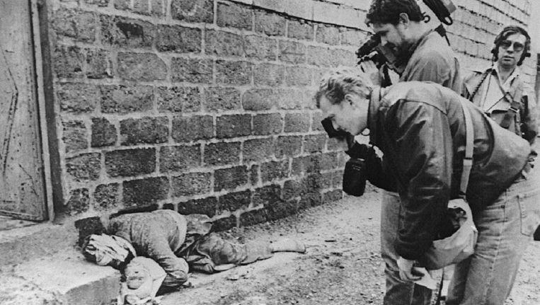 Maart 1988, Halabja. Westerse persfotografen bij een omgekomen Koerd met kind. Beeld AFP