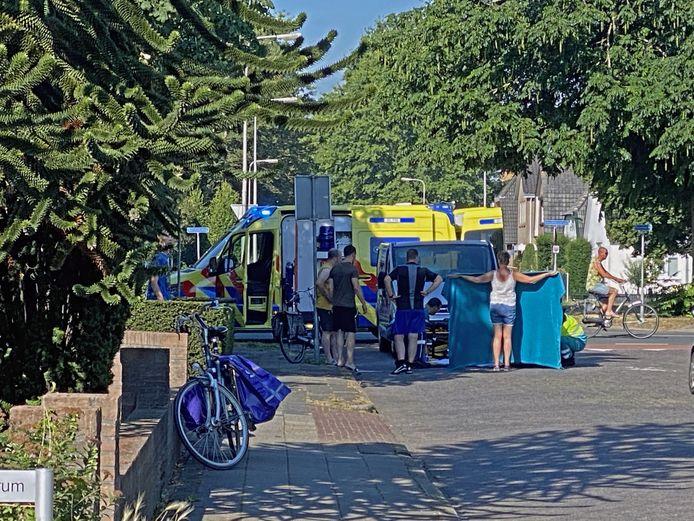 Ambulancepersoneel verzorgt de gewonde fietsster.