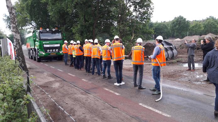 Bestuurders en wegenbouwers staan met helm op klaar voor de officiële openingshandeling van de reconstructie van de N324.