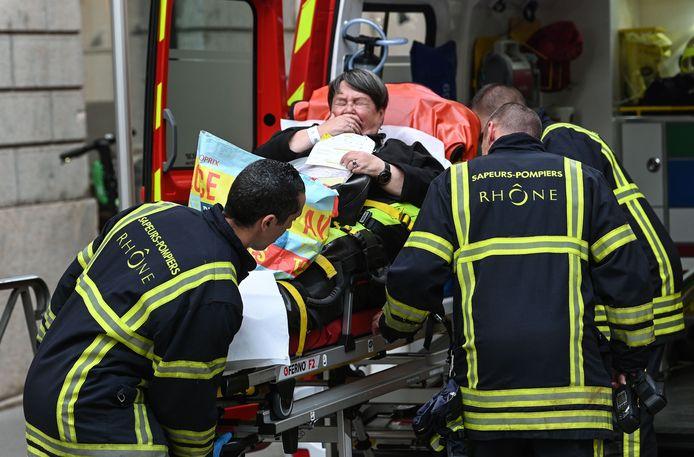 Een gewonde vrouw wordt weggebracht.