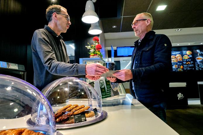 McDonald's-eigenaar Alec Delgorge (links) geeft vaste klant Cor van Arkel een kop koffie in het nagenoeg verlaten filiaal aan de Kerkeplaat in Dordrecht: ,,Gelukkig hebben er nogal wat medewerkers vakantie genomen.''