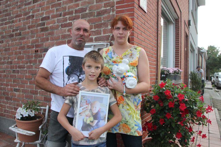 Alex Lanneau, Brina Dury en hun zoontje Alexiano met een foto van Tiziano. Ze zijn hun verdriet nog steeds aan het verwerken. Het bedrog is een nieuwe tegenslag.