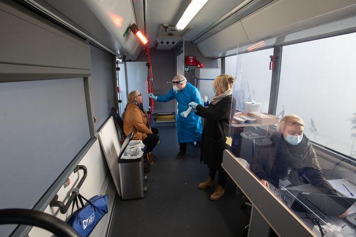 Inwoners laten zich op Urk in een mobiele teststraat van de GGD testen.