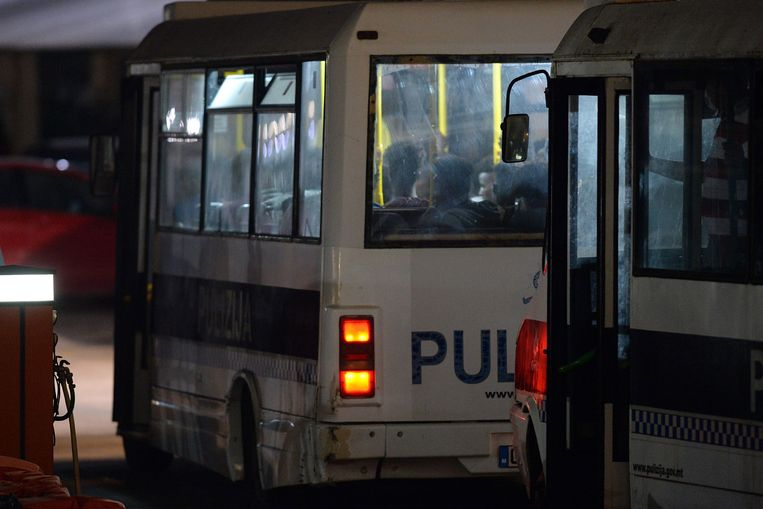 De migranten die van de Alan Kurdi afkomen, worden in politiebusjes weggebracht. Beeld AFP