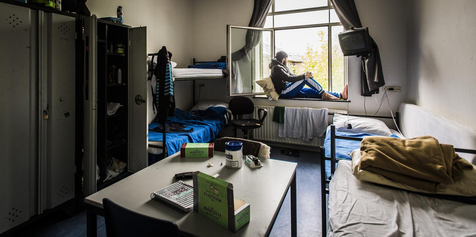 Een Syrische vluchteling zit in het raamkozijn van zijn kamer in het asielzoekerscentrum in Utrecht.
