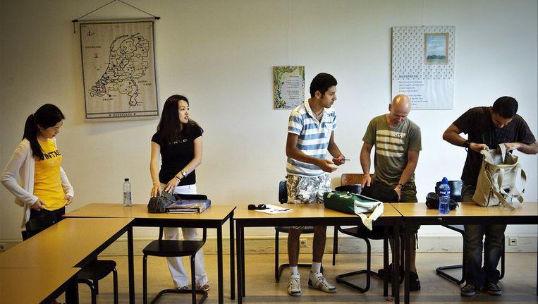 Buitenlandse studenten van verschillende nationaliteiten pakken hun tassen in na afloop van de Nederlandse les. © ANP Beeld