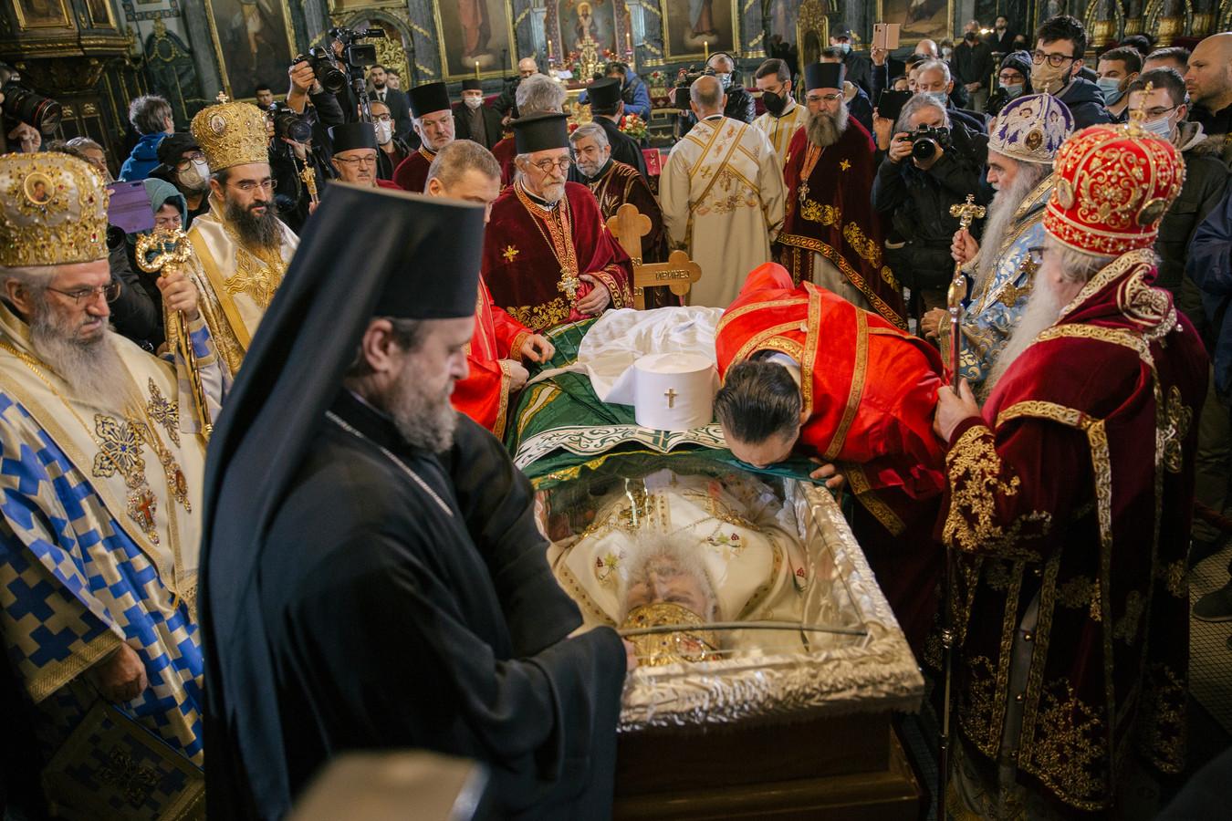 Servisch-Orthodoxe geestelijken betuigen de laatste eer aan de aan corona overleden patriarch Irinej in Belgrado.