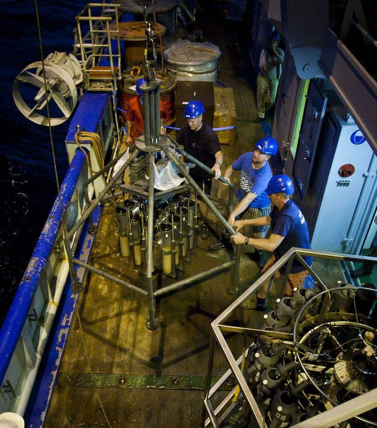 Technici Leon Wuis, Jan-Dirk de Visser en Martin de Vries hijsen de maanlander in duisternis boven water. Beeld Ronald Veldhuizen