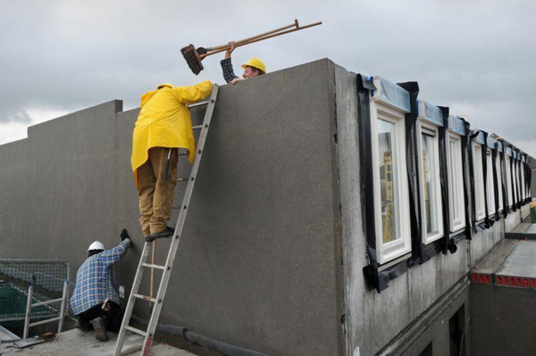 Bouwvakkers zijn aan de slag met een woningbouwhuis. Beeld null