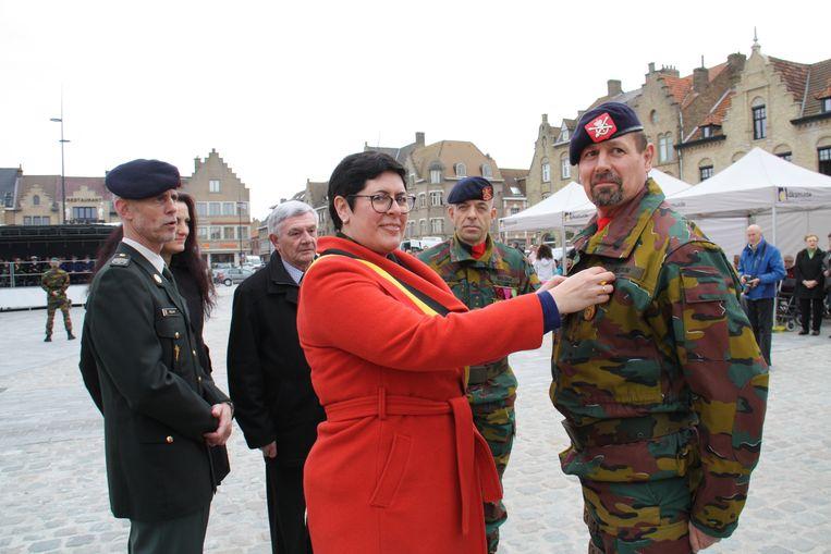 Medailleparade op de Grote Markt van Diksmuide om de militairen van het kwartier in Lombardsijde te danken voor hun inzet. Burgemeester Lies Laridon spelt de eerste medaille op