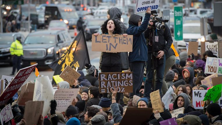 Amerikanen protesteren op het vliegveld van New York tegen het immigratiebeleid van Trump Beeld afp